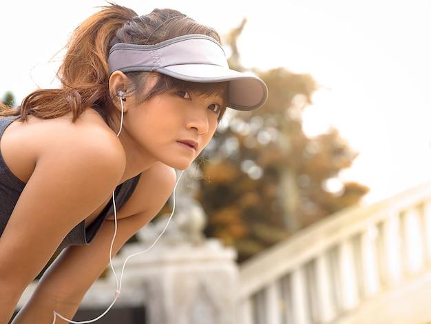 Jeune fille de sport se reposer et prendre une pause après le marathon courir, écouter de la musique