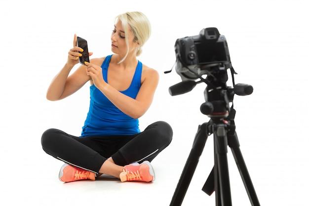 La jeune fille sportive aux cheveux blonds est assise devant la caméra et montre le téléphone