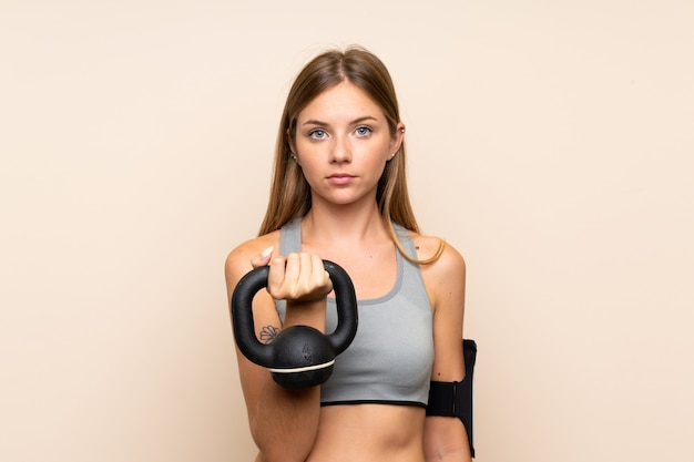 Jeune fille sportive blonde sur mur isolé faisant l'haltérophilie avec kettlebell et regardant vers l'avant