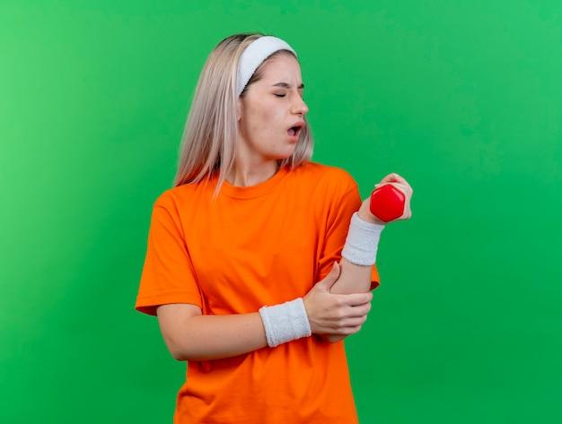 Une jeune fille sportive caucasienne douloureuse avec des bretelles portant un bandeau et des bracelets met la main sur le bras tenant l'haltère