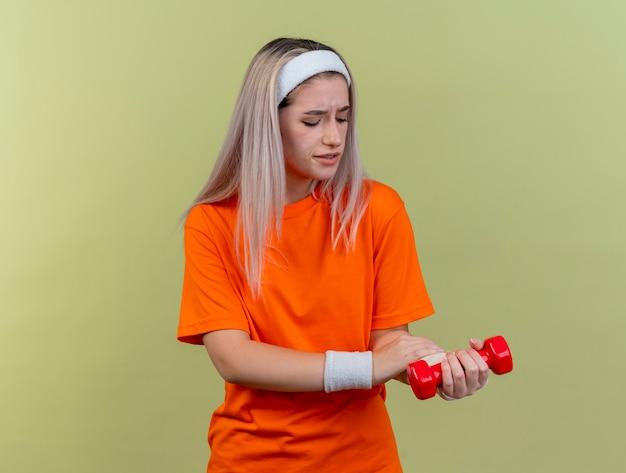 Une jeune fille sportive caucasienne douloureuse avec des bretelles portant un bandeau et des bracelets tient un haltère et regarde à portée de main