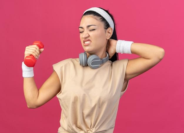 Jeune fille sportive caucasienne douloureuse portant un bandeau et des bracelets avec des écouteurs autour du cou soulevant des haltères en gardant la main derrière le cou avec les yeux fermés isolés sur un mur rose