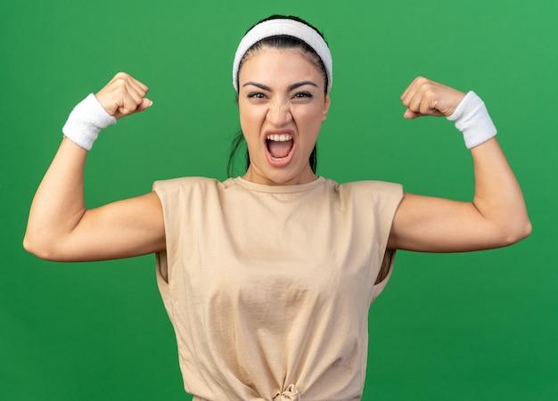 Jeune fille sportive caucasienne furieuse portant un bandeau et des bracelets faisant un geste fort criant isolé sur un mur vert
