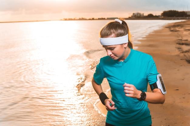 Jeune fille sportive en cours d'exécution sur la plage au lever du soleil le matin