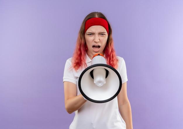 Jeune fille sportive criant au mégaphone avec une expression agressive debout sur un mur violet