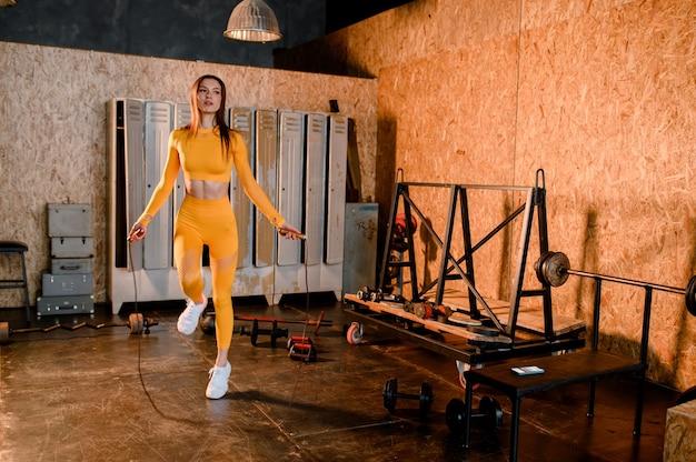 Jeune fille sportive dans un uniforme de sport jaune, préparez-vous pour une séance d'entraînement moderne de style loft