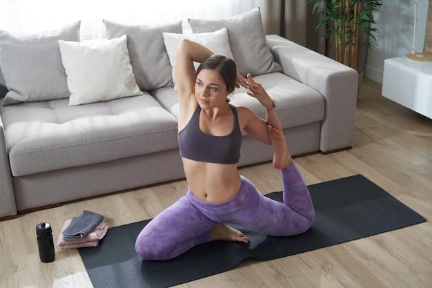 Jeune fille sportive faisant des exercices d'étirement du yoga assis sur un tapis près du canapé dans le salon à la maison