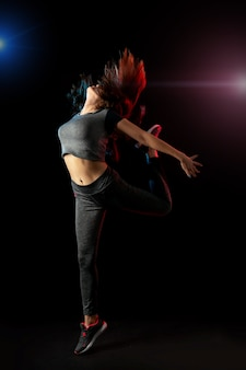 Jeune fille sportive mince sautant sur le mur noir.