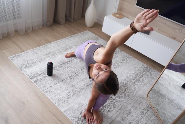 Jeune fille sportive pratiquant le yoga à la maison dans le salon concept sport et fitness vue d'en haut