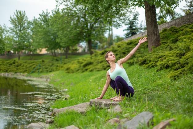 Une jeune fille sportive pratique le yoga sur une pelouse verte au bord de la rivière, la posture du yoga assans. méditation et unité avec la nature