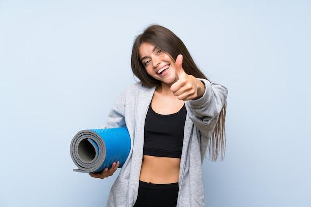 Jeune fille sportive avec tapis sur fond bleu isolé avec le pouce levé parce que quelque chose de bien est arrivé