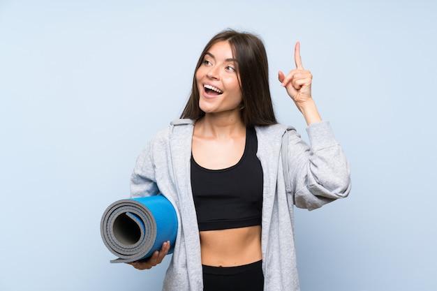 Jeune fille sportive avec tapis visant à réaliser la solution tout en levant le doigt