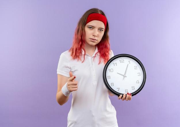 Jeune fille sportive tenant horloge murale avec visage sérieux pointant avec le doigt debout sur le mur violet