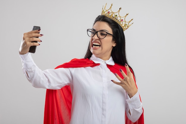 Jeune fille de super-héros caucasien en colère portant des lunettes et une couronne en gardant la main dans l'air prenant selfie isolé sur fond blanc avec espace de copie