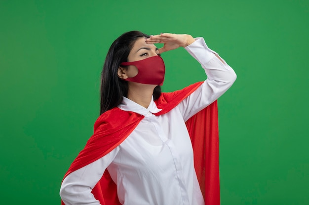 Jeune fille de super-héros caucasien debout en vue de profil en mettant la main sur la tête à la recherche directe dans la distance mur vert isolé avec copie espace