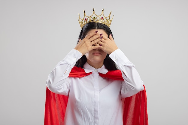 Jeune fille de super-héros caucasien portant des lunettes et une couronne couvrant les yeux avec les mains isolés sur fond blanc