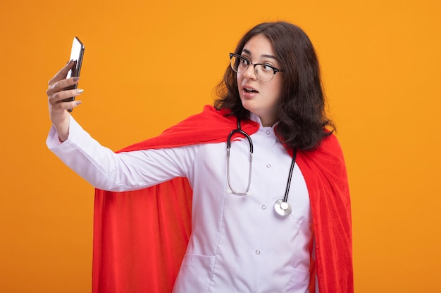 Jeune fille de super-héros caucasienne impressionnée en cape rouge portant un uniforme de médecin et un stéthoscope avec des lunettes prenant un selfie isolé sur un mur orange