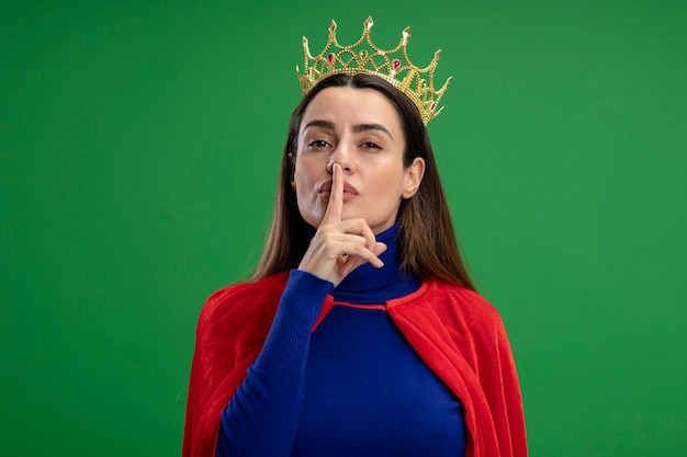 Jeune fille de super-héros portant couronne montrant le geste de silence isolé sur vert