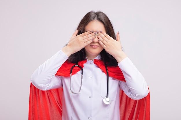 Jeune fille de super-héros de race blanche portant un uniforme de médecin et un stéthoscope couvrant les yeux avec les mains