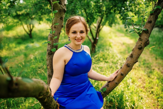 Jeune fille en surpoids à la robe bleue a posé fond jardin printanier assis sur l'arbre.
