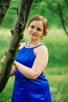 Jeune fille en surpoids à la robe bleue a posé fond jardin printanier.