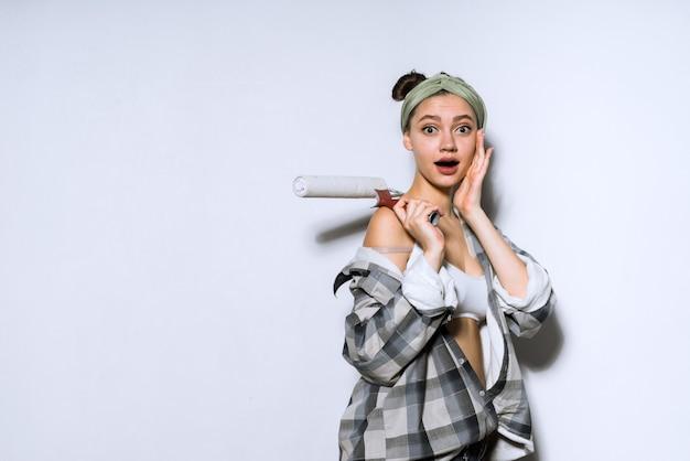 Jeune fille surprise faisant des réparations dans un nouvel appartement, tenant un rouleau pour peindre les murs