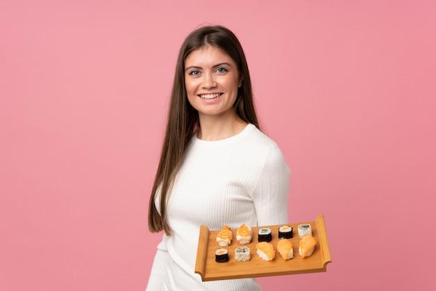 Jeune fille avec sushi sur fond rose isolé souriant beaucoup