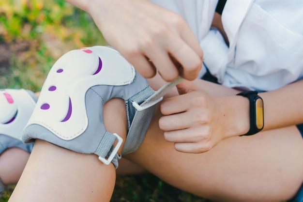Jeune fille sympa, mettre un équipement de protection avant le patinage à roulettes dans le parc