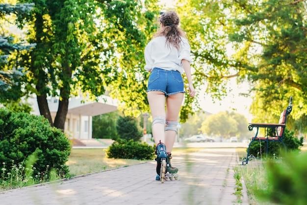 Jeune fille sympa patinage dans le parc. fermer. concept de repos et de plaisir