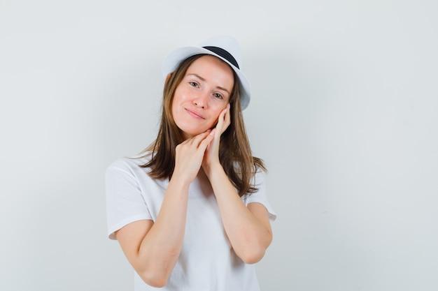 Jeune fille en t-shirt blanc, chapeau appuyé contre la joue sur la paume et à la belle vue de face.