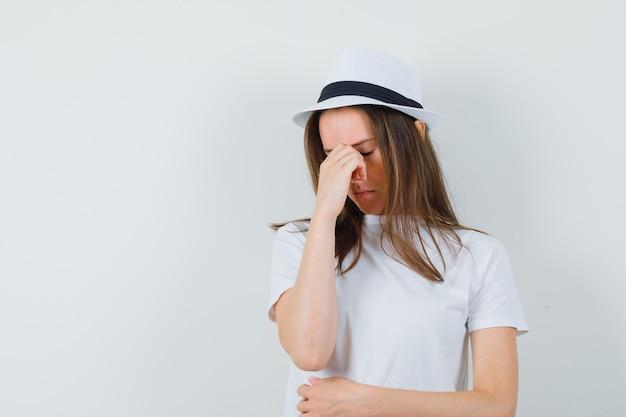 Jeune fille en t-shirt blanc, chapeau frottant les yeux et le nez et à la colère, vue de face.