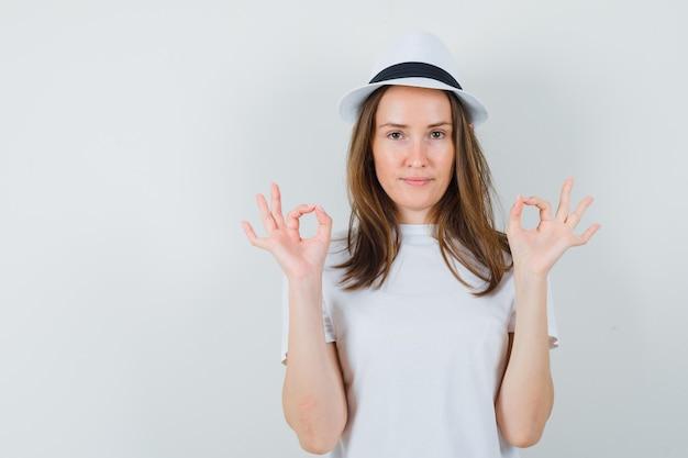 Jeune fille en t-shirt blanc, chapeau montrant un geste correct et à la vue de face, confiant.