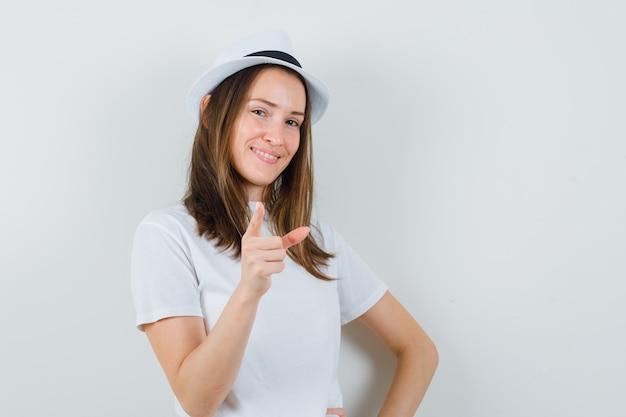 Jeune fille en t-shirt blanc, chapeau pointant et regardant confiant, vue de face.