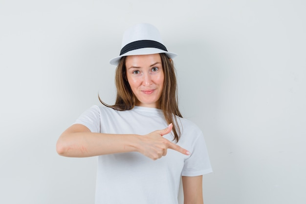 Jeune fille en t-shirt blanc, chapeau pointant vers le bas et regardant confiant, vue de face.
