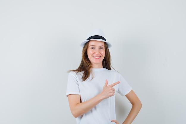 Jeune fille en t-shirt blanc, chapeau pointant vers le coin supérieur droit et regardant jovial, vue de face.