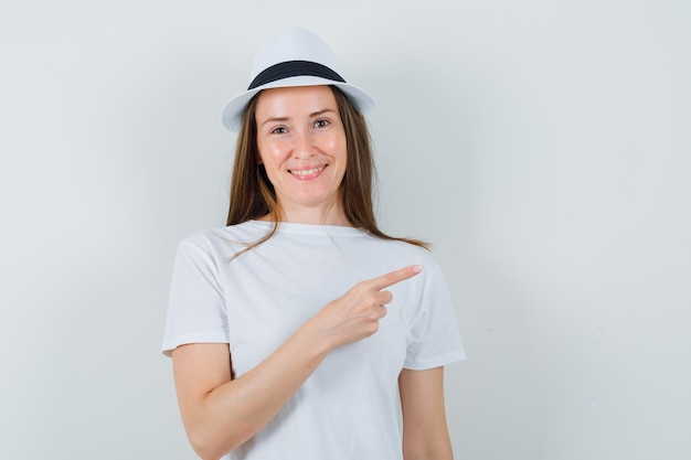 Jeune fille en t-shirt blanc, chapeau pointant vers le coin supérieur droit et à la vue de face, heureux.
