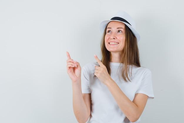 Jeune fille en t-shirt blanc, chapeau pointant vers le coin supérieur gauche et à la joyeuse vue de face.