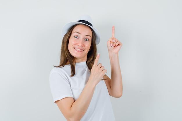 Jeune fille en t-shirt blanc, chapeau pointant vers le haut et à la béatitude, vue de face.