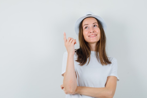 Jeune fille en t-shirt blanc, chapeau pointant vers le haut et à l'espoir, vue de face.