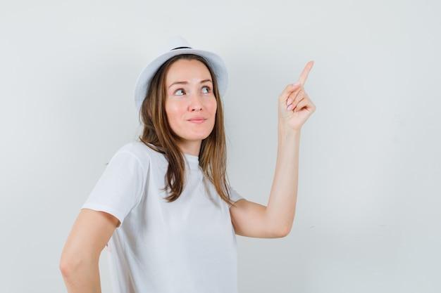 Jeune fille en t-shirt blanc, chapeau pointant vers le haut et à la vue de face, heureux.
