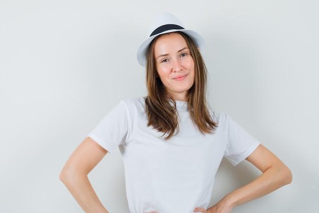 Jeune fille en t-shirt blanc, chapeau posant en position debout et à la glamour, vue de face.