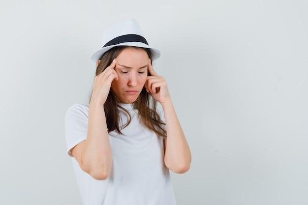 Jeune fille en t-shirt blanc, chapeau se frottant les tempes et à la fatigue, vue de face.