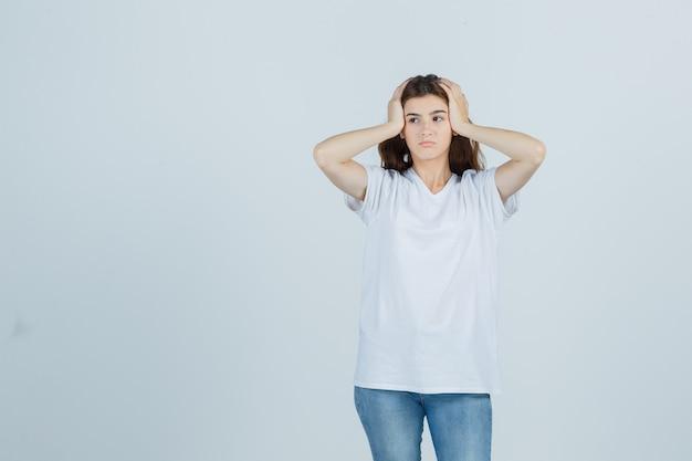 Jeune fille en t-shirt blanc, main dans la main sur la tête et à la vue réfléchie, de face.
