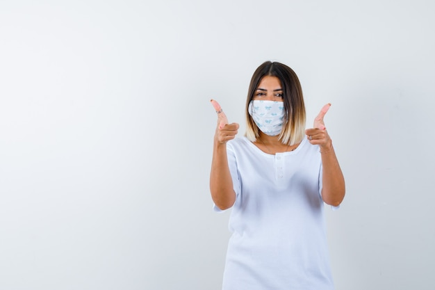 Jeune fille en t-shirt blanc et masque montrant deux pouces vers le haut et à la joyeuse vue de face.