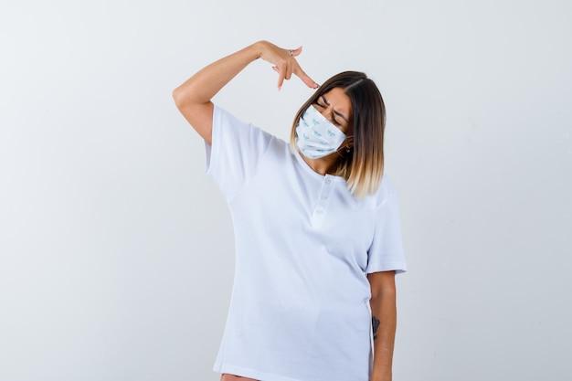 Jeune fille en t-shirt blanc, masque montrant le geste du pistolet près de la tête et l'air confiant, vue de face.