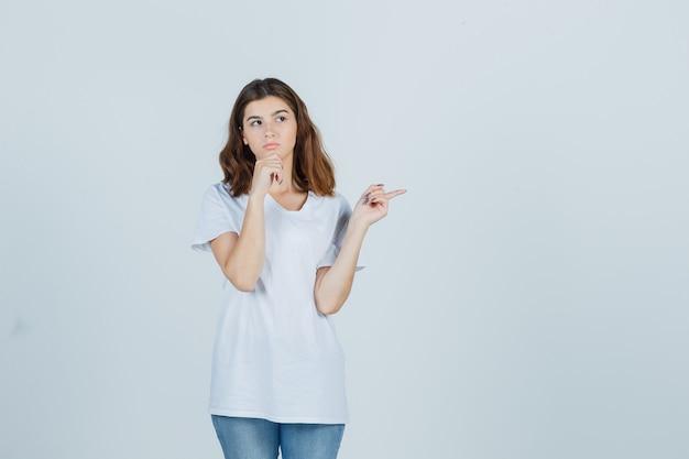 Jeune fille en t-shirt blanc pointant de côté, soutenant le menton sur la main et regardant pensif, vue de face.