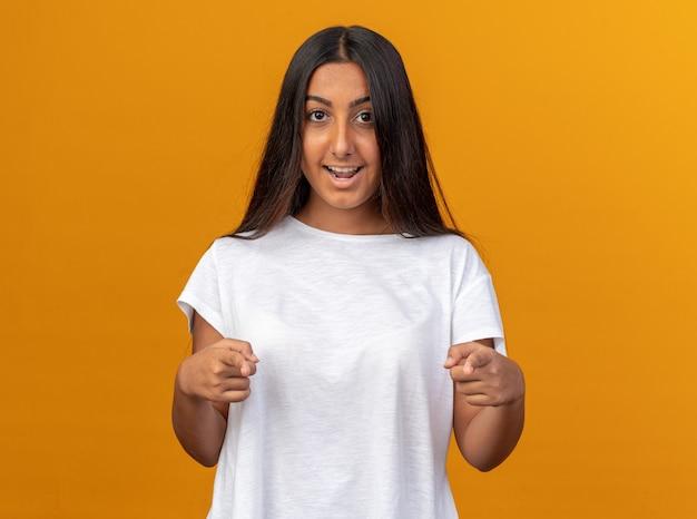 Jeune fille en t-shirt blanc pointant heureux et positif avec l'index à la caméra souriant joyeusement debout sur fond orange