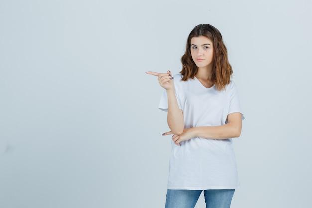 Jeune fille en t-shirt blanc pointant vers le côté gauche et regardant pensif, vue de face.