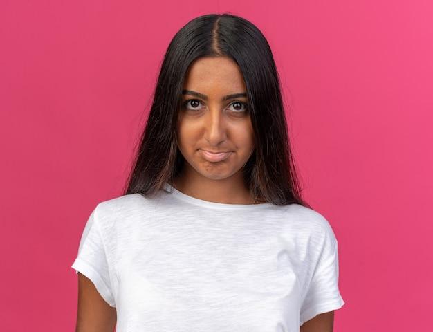Jeune fille en t-shirt blanc regardant la caméra avec une expression triste pinçant les lèvres debout sur fond rose