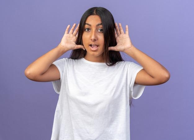 Jeune fille en t-shirt blanc regardant la caméra heureuse et surprise tenant les paumes ouvertes sur ses oreilles, debout sur fond bleu